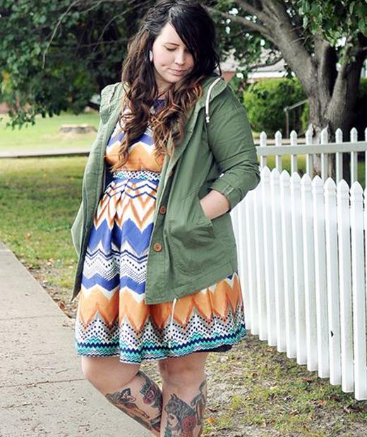 Kaelah Bee porte un gilet kaki et une robe colorée